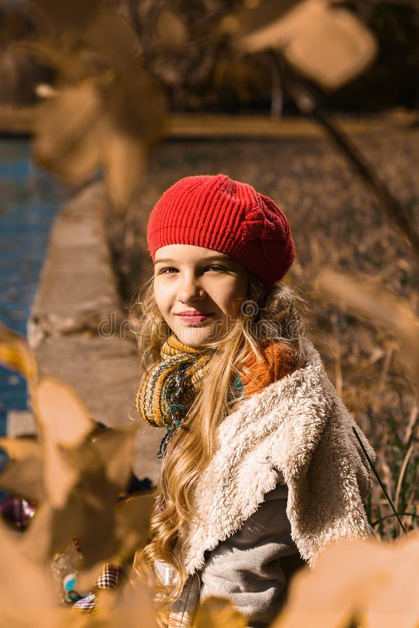Autumn portrait of beautiful young girl in red hat royalty free stock images