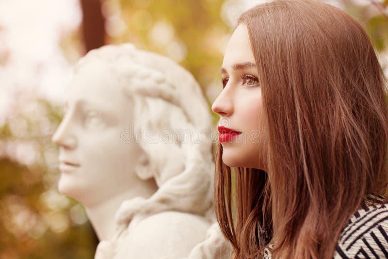 Autumn Portrait der hübschen Frau und der Marmorstatue draußen lizenzfreie stockfotos