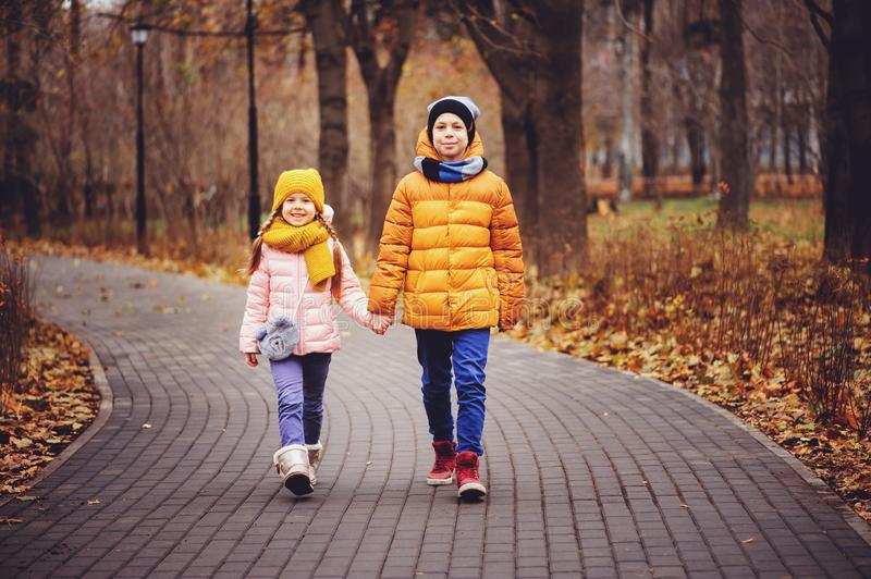 autumn portrait of happy brother and sister walking the road in sunny park stock photo