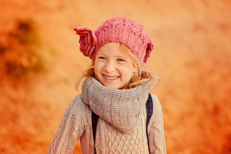 Autumn portrait of happy child girl in knitted hat and scarf. Autumn portrait of happy child girl in oink knitted hat and grey scarf stock photos
