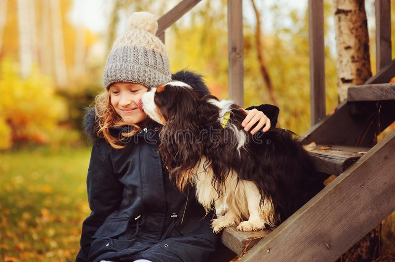 Autumn portrait of happy kid girl playing with her spaniel dog in the garden. Sitting on wooden stairs and hugs stock images