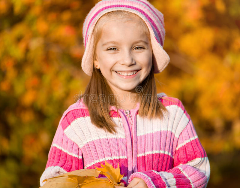Autumn portrait of a little girl. Pretty smiling girl against the leaves of mountain ash royalty free stock images