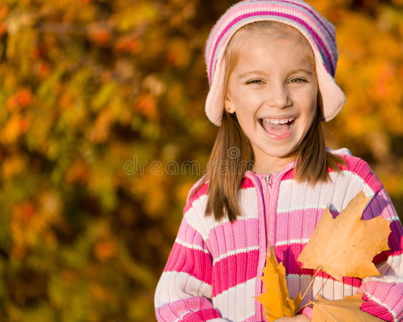 Autumn portrait of a little girl. Smiling cute girl against the leaves of mountain ash royalty free stock photos