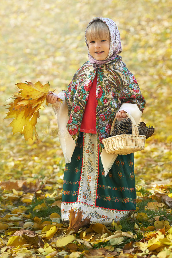 Autumn portrait of the little girl in the traditional russian sarafan and headscarf gathering yellow leaves and pinecones royalty free stock images