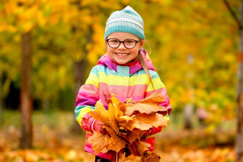 Autumn portrait of a little girl with yellow leaves in her hands in park royalty free stock photos