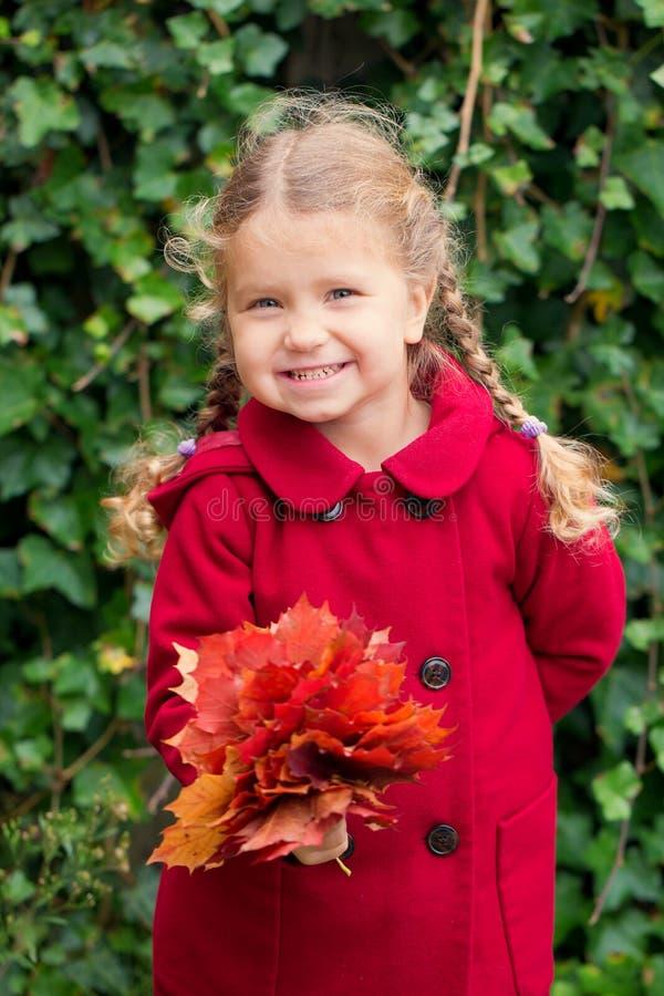 Autumn Portrait Niño sonriente que sostiene el ramo de hojas de otoño imagenes de archivo