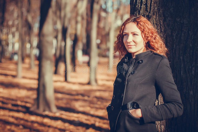 Autumn portrait. Of a smiling girl standing near a tree in the park royalty free stock photography