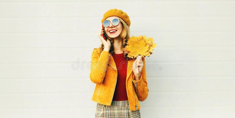 Autumn portrait smiling woman calling on phone holding yellow maple leaves wearing french beret on city street over gray wall stock photography
