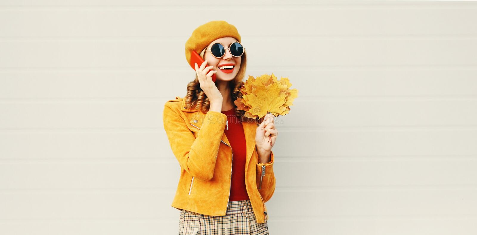 Autumn portrait smiling woman calling on phone holding yellow maple leaves wearing french beret on city street over gray wall stock images