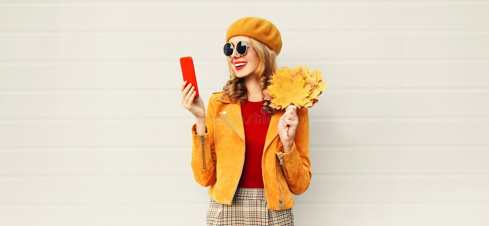 Autumn portrait smiling woman holding phone, yellow maple leaves wearing french beret on city street over gray wall stock image