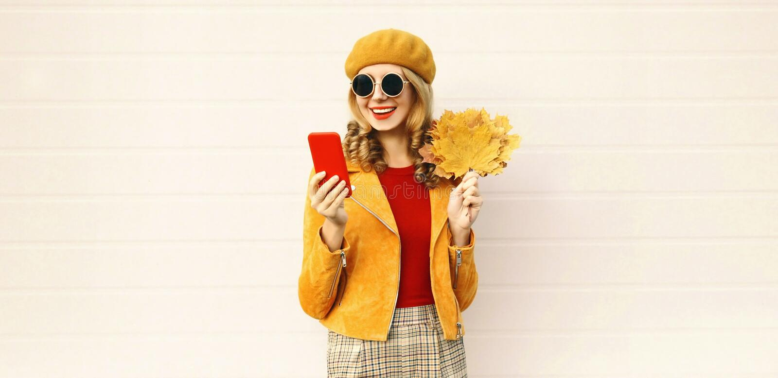 Autumn portrait smiling woman holding phone, yellow maple leaves wearing french beret on city street over gray wall royalty free stock images