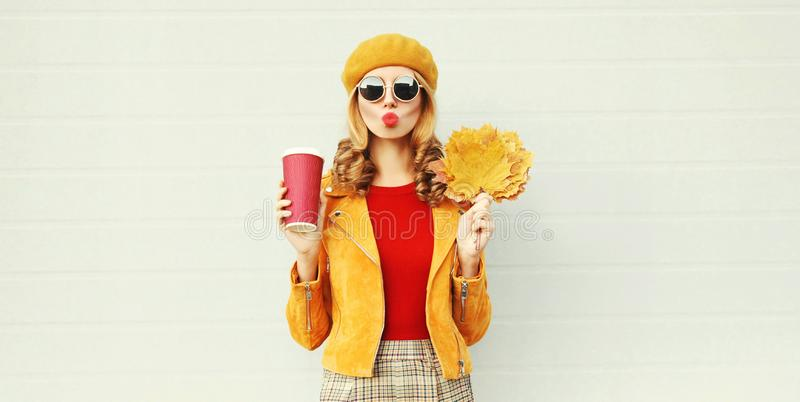 Autumn portrait woman with yellow maple leaves, coffee cup blowing red lips sending sweet air kiss over gray wall royalty free stock photography