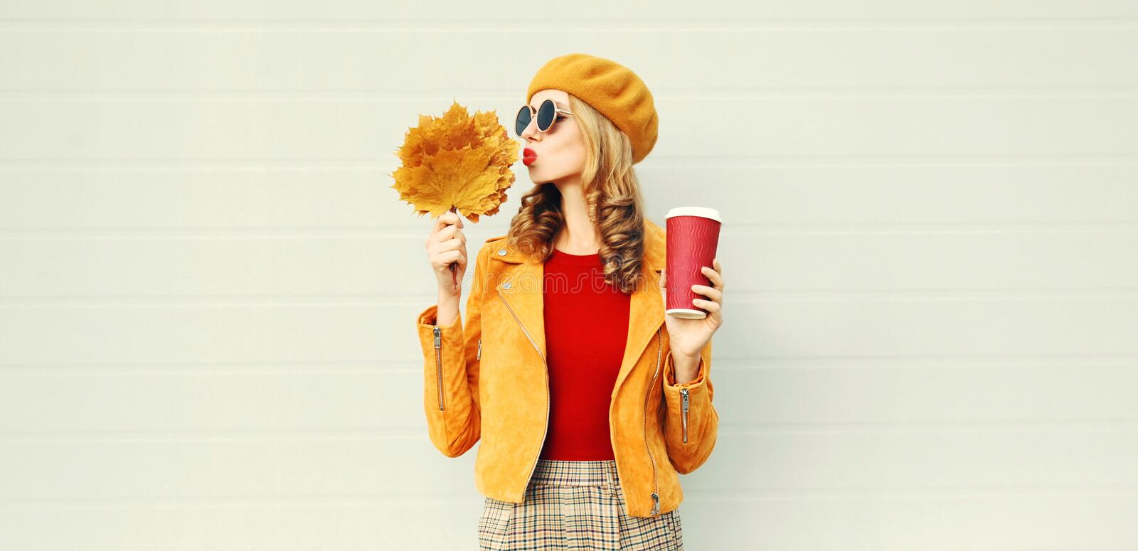 Autumn portrait woman with yellow maple leaves, coffee cup blowing red lips sending sweet air kiss over gray wall royalty free stock image