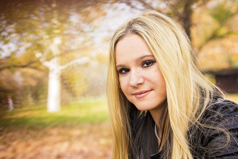 Autumn portrait of a young blond woman royalty free stock image