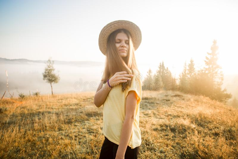 Autumn portrait of young woman in straw hat walk in morning on top of hill with mountains background. Harmony with stock images