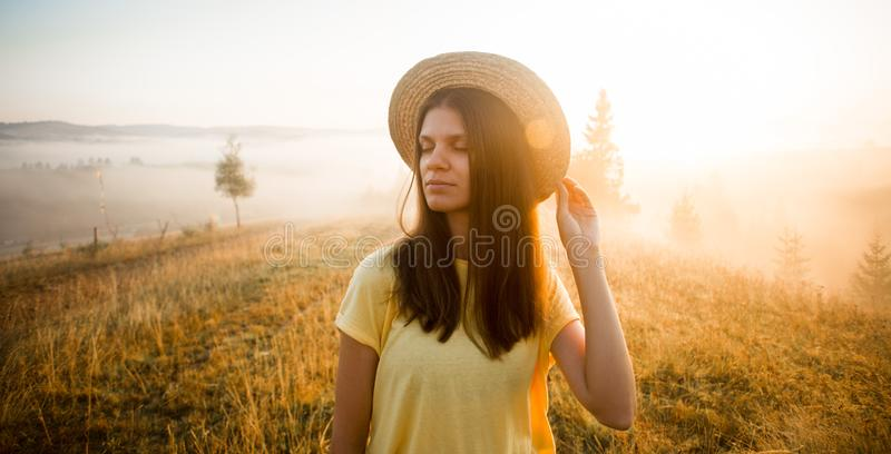 Autumn portrait of young woman in straw hat walk in morning on top of hill with mountains background. Inspiration. stock image