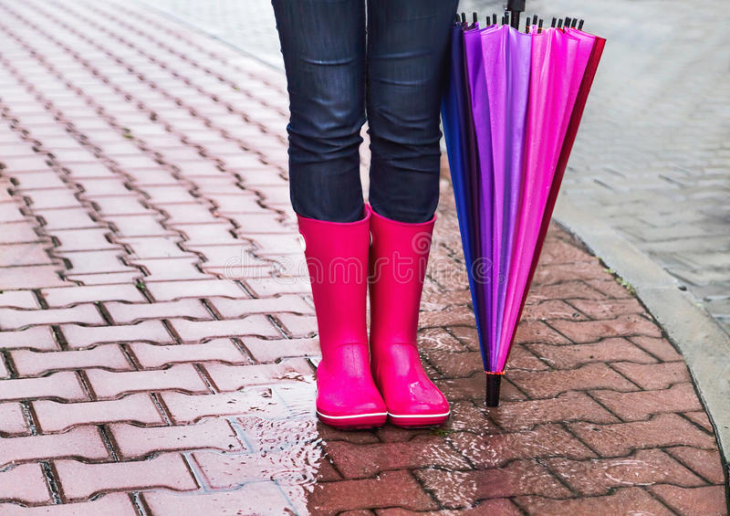 Autumn. Protection in the rain. Woman (girl) wearing pink rubber boots and has colorful umbrella. Street, city. Raindrops. Copy space. Place for message royalty free stock photos