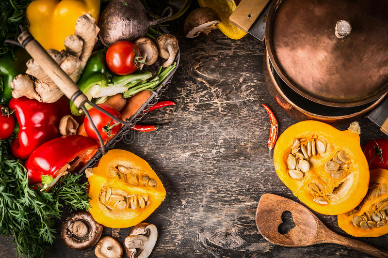 Autumn pumpkin dish cooking preparation with cooking pot ,vegetables and mushrooms on rustic wooden background, top view, frame. royalty free stock photography