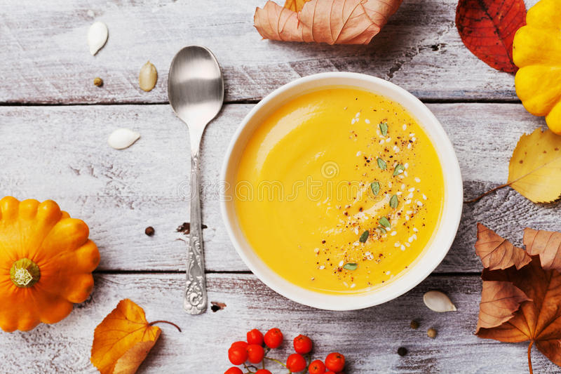 Autumn pumpkin soup decorated seeds and thyme in white bowl on rustic wooden table top view. Cozy lifestyle shot for halloween. stock images
