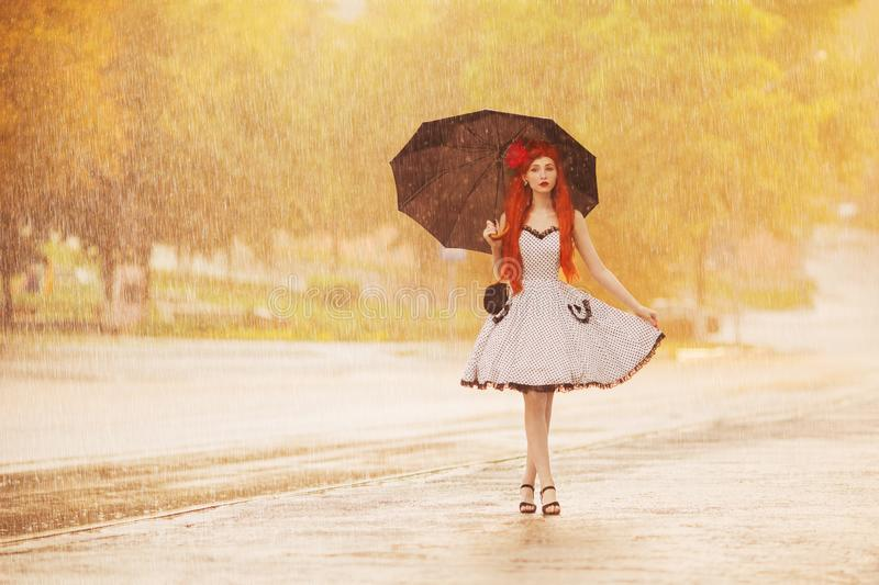 Autumn rain. Redhead girl in dress hold umbrella. Raining in city. Raindrop background. Wet umbrella protection. Woman was caught royalty free stock photos