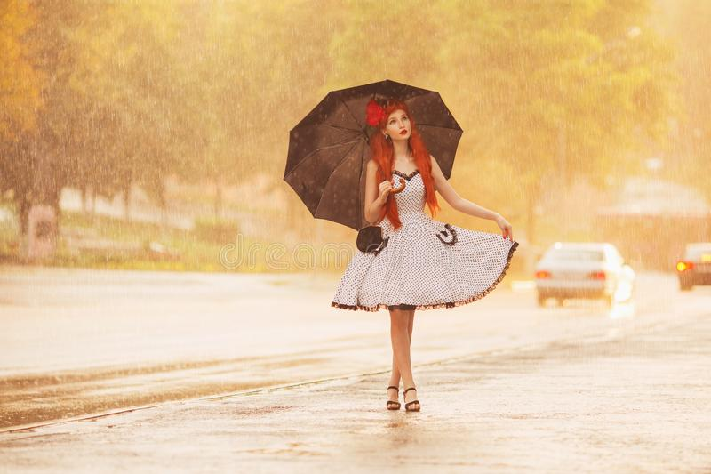 Autumn rain. Retro redhead girl in polka dots dress hold black umbrella. Raining in city. Wet umbrella. Woman was caught in summer stock photo