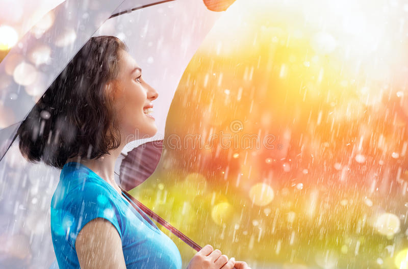 Autumn rain. A smiling woman happy rain