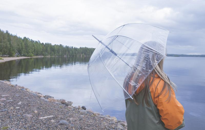 Autumn rain or wet weather. Lonely girl in grey-orange jacket hold umbrella. Raining on the lake. Wet umbrella against the stock image