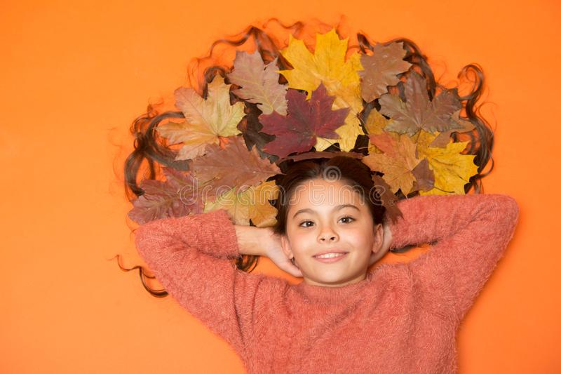 Autumn is reason to smile. Autumn look of small beauty model. Happy girl with autumn leaves in long hair. Natural beauty. Hair salon. Autumn is season when royalty free stock images