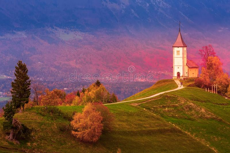 Sunset with church on top of hill, Slovenia. Autumn red sunset panorama with Saints Primus and Felician Church on top of hill in Jamnik, Slovenia countryside stock image