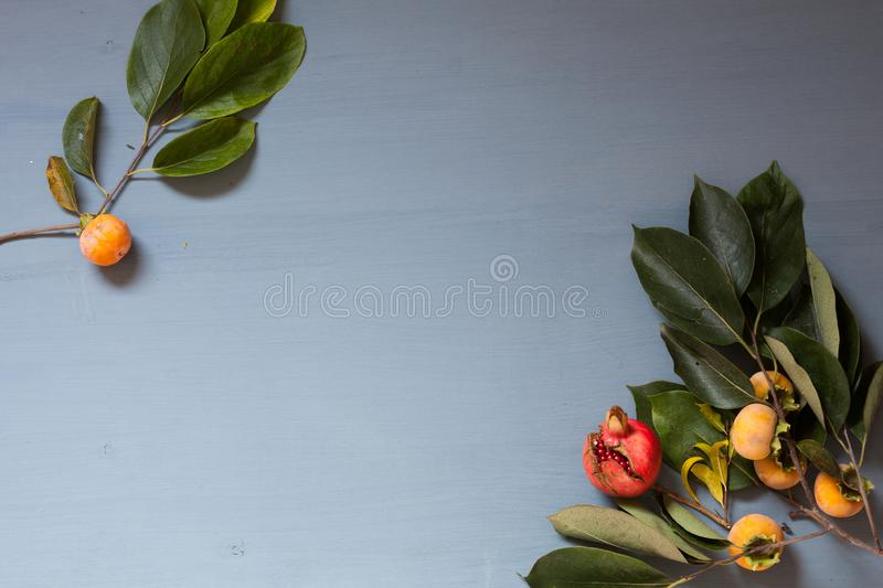 Autumn red and yellow leaves of the fruit pomegranate persimmon stock photography