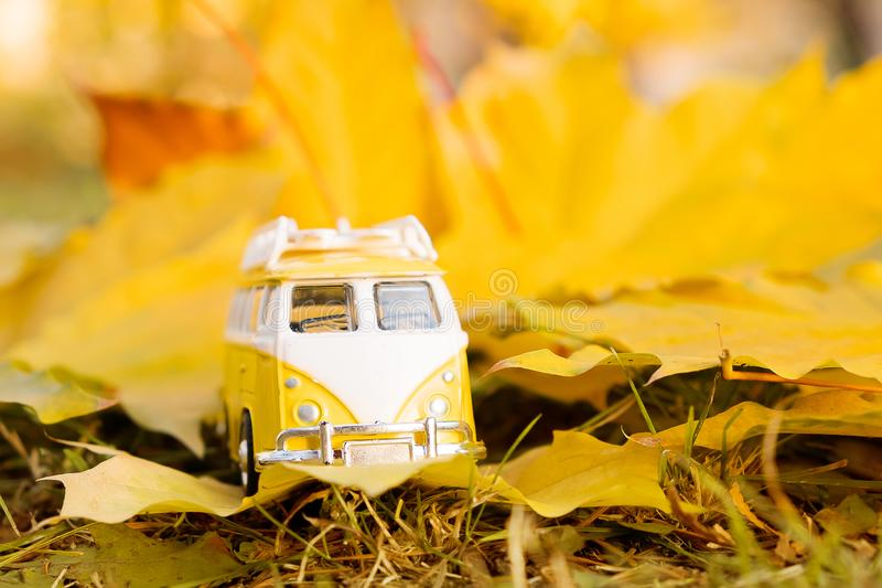 Autumn retro yellow van bus on autumn maple leaf background. Funny retro toy car. Autumn travel and vacation concept. royalty free stock photography