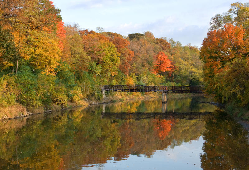 Autumn River. Photograph of the colors of autumn reflected in a slow moving river with an interesting foot bridge crossing. Taken in the early morning light stock photography
