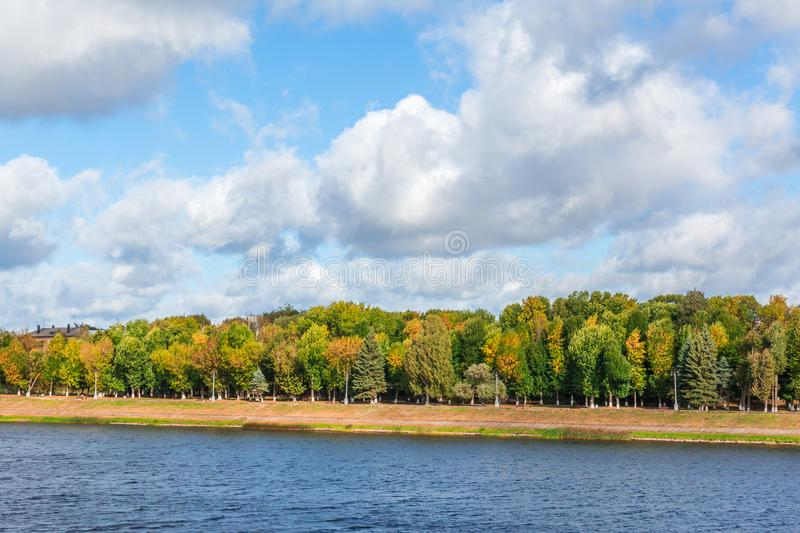 Autumn river landscape. Picturesque clouds. Yellowing leaves on trees royalty free stock photography