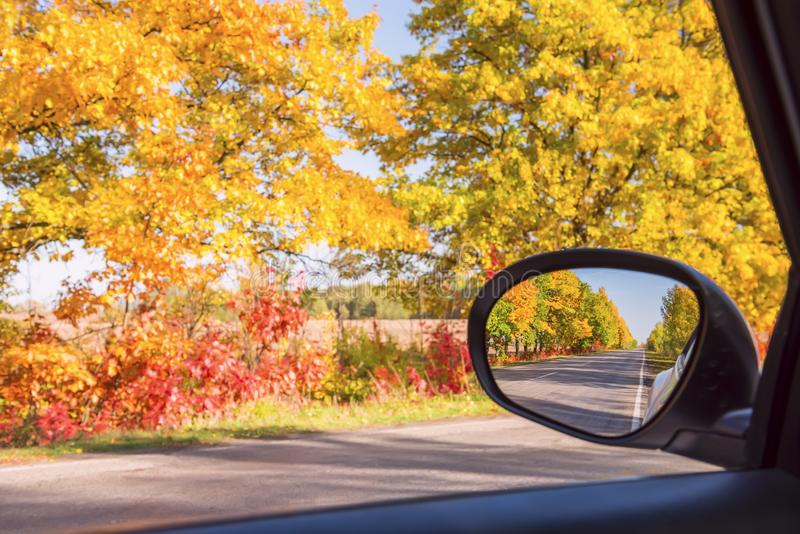 Autumn road with colorful bright trees and a car mirror with road reflections. Change of seasons stock images