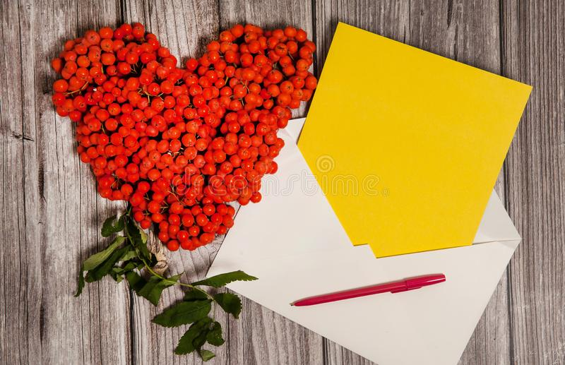 Autumn romantic composition. Heart made of orange Rowan berries, paper blank, envelope, pen on wooden background. royalty free stock photography