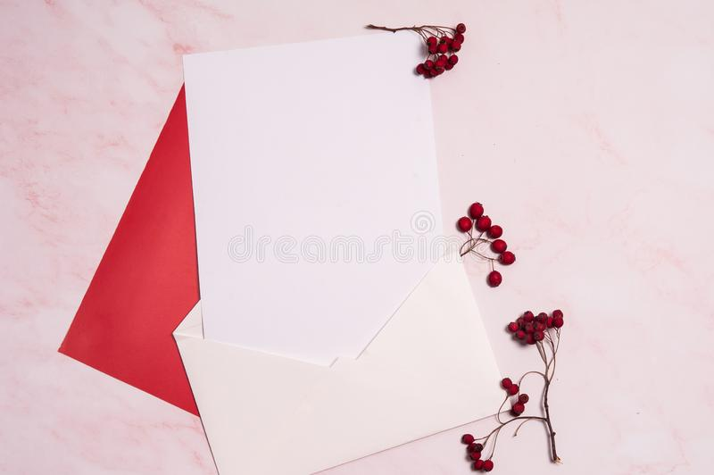 Paper blank, envelope, branches with red hawthorn berries on a pink background. Autumn romantic composition. Paper blank, envelope, branches with red hawthorn royalty free stock photo