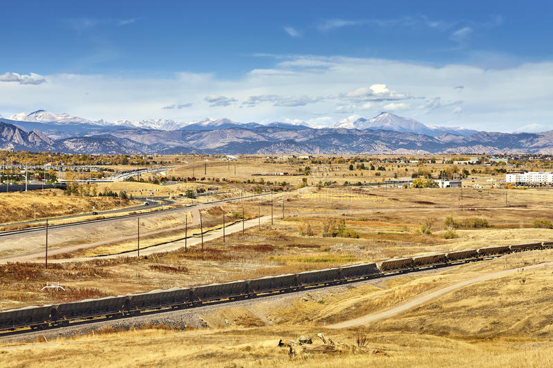 Autumn rural landscape with cargo train and Rocky Mountains. Autumn rural landscape with cargo train and Rocky Mountains in distance, Colorado, USA royalty free stock image