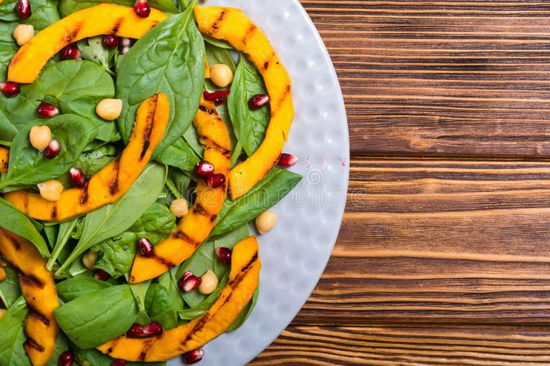 Autumn salad with pumpkin spinach , pomegranate and chickpea . Healthy vegan food. Autumn salad with pumpkin , spinach , pomegranate and chickpea . Healthy vegan royalty free stock photo