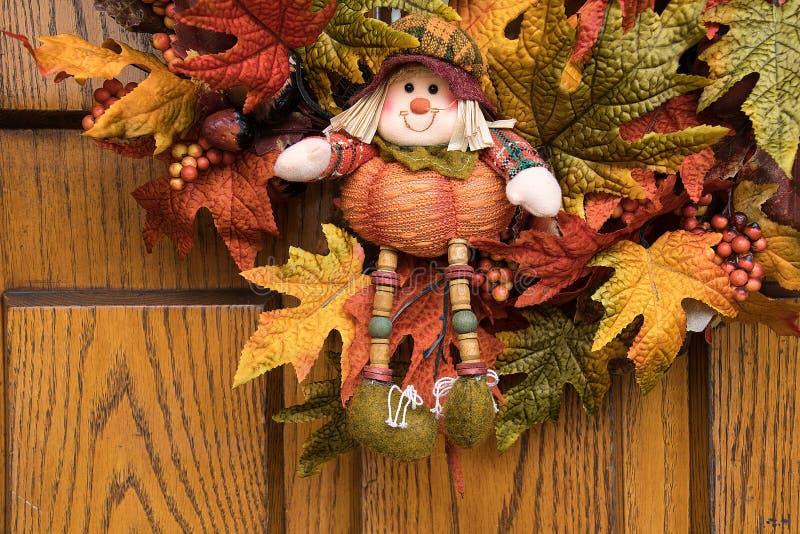 Autumn scarecrow doll on door wreath royalty free stock photography