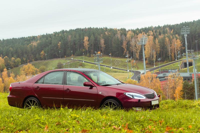 Autumn scene with Cherry red 4 door family d-class sedan Toyota Camry royalty free stock images