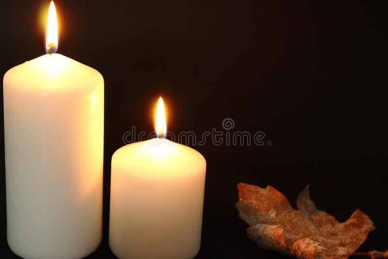 Autumn scene of two lighted white veils and a leaf. stock images