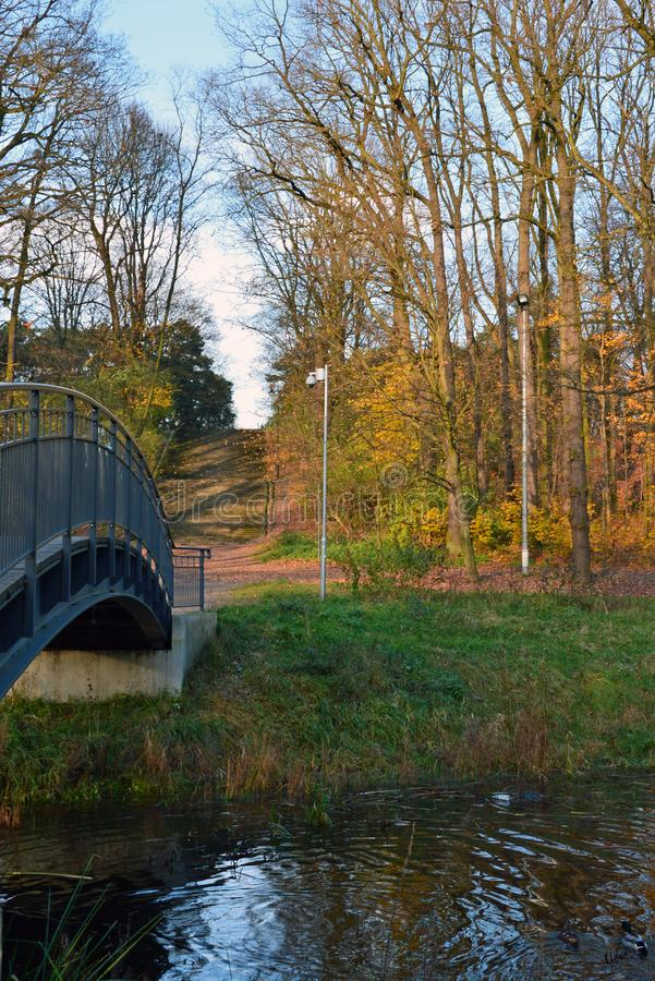Autumn scenery with a bridge in a park royalty free stock image