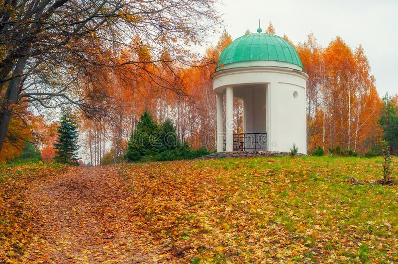 Autumn scenery with colored trees and white alcove, Arboretum Oleksandriya, Bila Tserkva, Ukraine. Fall olexandria gazebo vivid multicolored seasonal autumnal royalty free stock photos