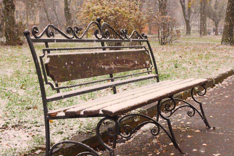 Autumn Scenery: Gammal trädgårdbänk i den sena nedgången som täckas av första snö Fors i Oktober royaltyfri foto