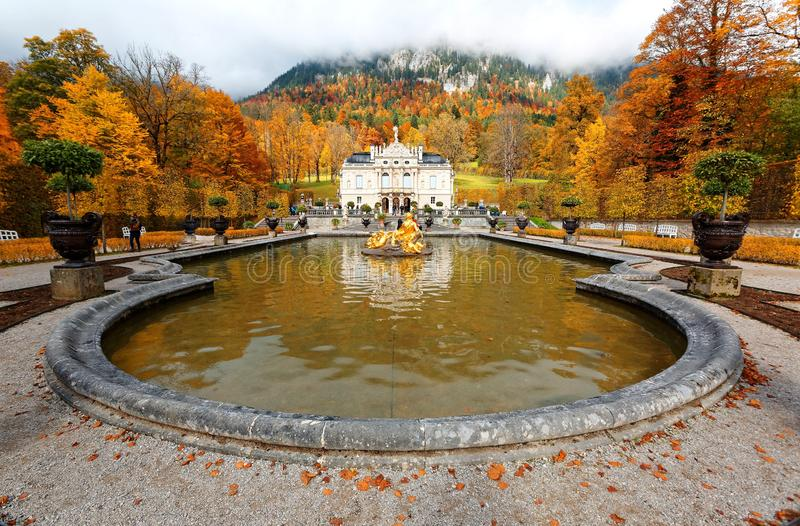 Autumn scenery of Linderhof Palace in Bavaria Germany, with view of a golden statue in the circular fountain pond royalty free stock photos