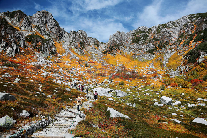 Autumn scenery of rugged mountain peaks and a hiking trail by the mountainside in Senjojiki Cirque. Of Japanese Central Alps National Park, Nagano, Japan royalty free stock images