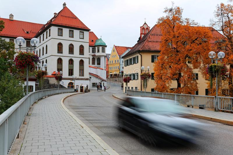 Autumn scenery at a street corner in the Old Town of Fussen, with a car driving on a bridge royalty free stock photos
