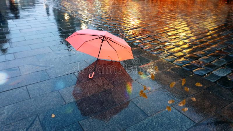 Autumn season city light pink umbrella rainy season street evening lightening blurring bokeh city people walking. Autumn evening in city street cafe cup of royalty free stock images