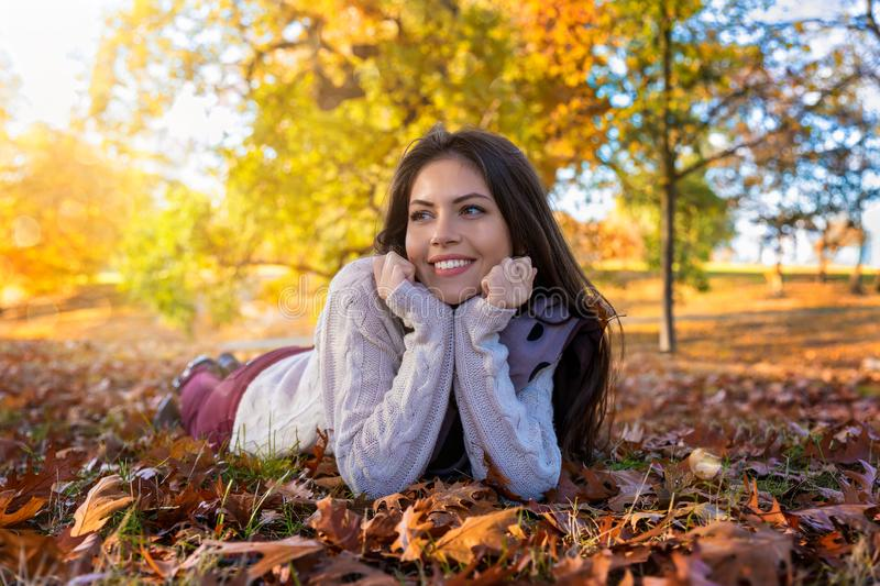 Woman lying down in a park during fall time in October royalty free stock photo