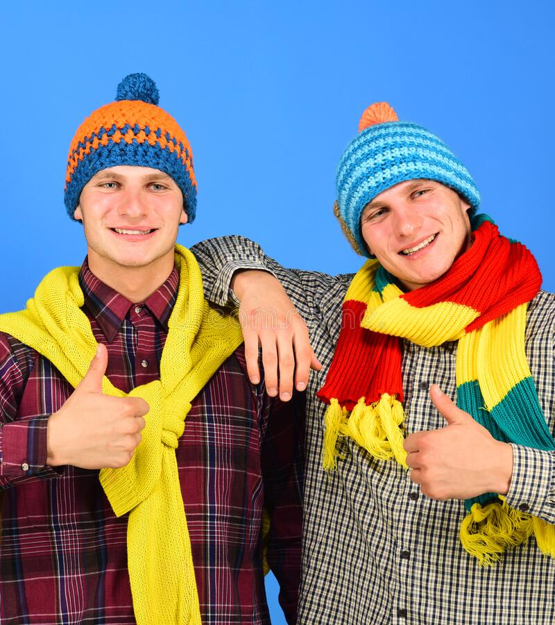 Autumn season and friendship. Siblings show thumbs up and hug. Guys in knitted scarves and hats on bright blue background, copy space. Twins with happy faces stock image